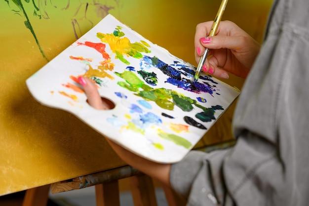 Künstlerin mischt farben auf der palette maler im studio schöpfer macht kunstwerk