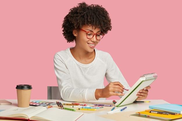 Künstlerin mit afro-frisur, erfreut gesichtsausdruck, hält notizbuch