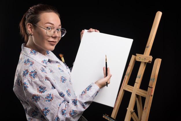 Künstlerin zeigt ihre leinwand mit pinsel auf schwarzem hintergrund