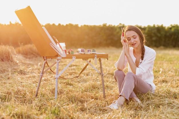Künstlerische frau, die auf dem gras sitzt
