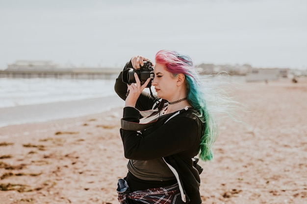 Künstlerische frau, die ein foto an einem strand macht