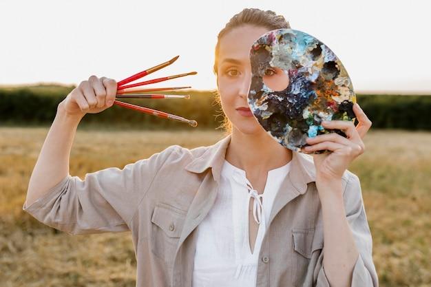 Künstlerische junge frau, die pinsel hält