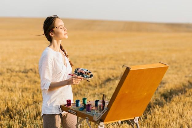 Künstlerische junge frau, welche die luft glaubt