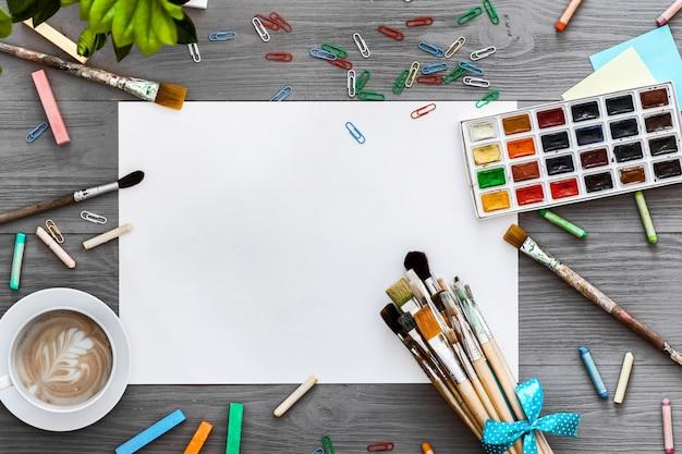Künstlerische kreative hintergrundkunstwerk liefert und modell leeres papier, flaches legen