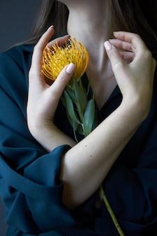 Künstlerische mädchenhände, die einen orange protea halten