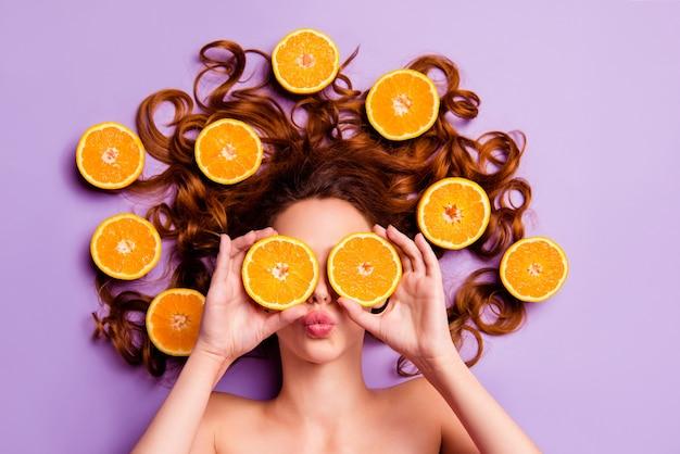 Künstlerische rothaarige frau, die mit orangen in ihren haaren aufwirft