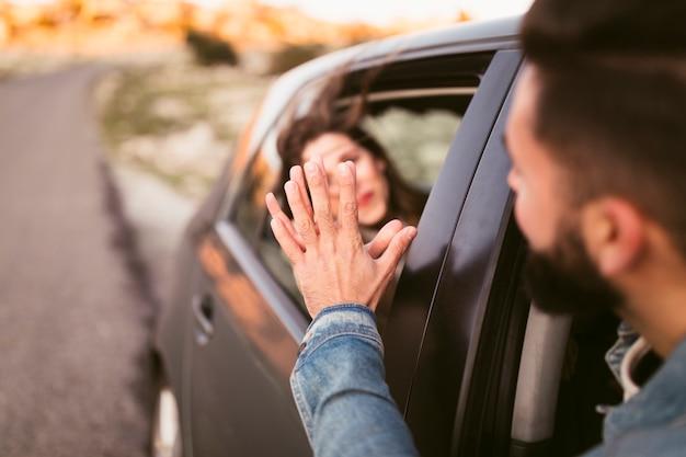 Künstlerischer fotomann und -frau, die hand außerhalb des autos hält