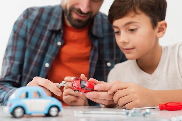 Künstlerischer fotosohn, der spielzeugautos mit vater repariert
