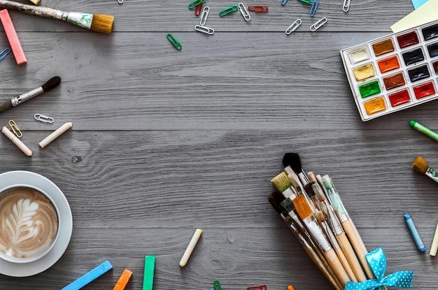 Künstlerisches kreatives hintergrundkunstwerk liefert und leeres papier, flach gelegt