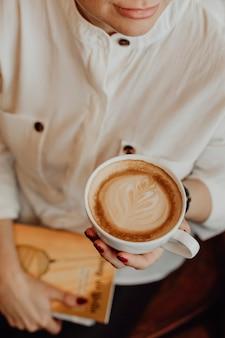 Künstlerisches mädchen, das eine tasse kaffee trinkt