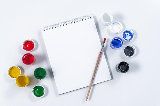 Künstlerisches modell auf einem weißen hintergrund mit platz für text. zeichenwerkzeuge: farbige acrylfarbe