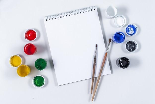 Künstlerisches modell auf einem weißen hintergrund mit platz für text. zeichenwerkzeuge, farbige acrylfarbe