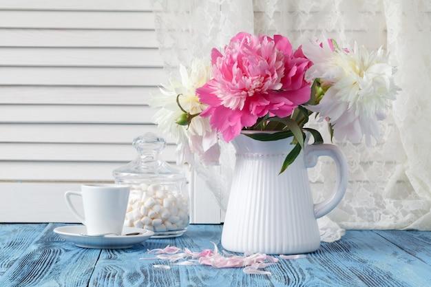 Künstlerisches stillleben mit pfingstrosen und einer tasse kaffee und blütenblättern
