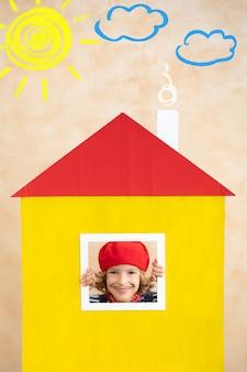 Künstlerkind, das im papierhaus versteckt hält. bleib zuhause. Premium Fotos
