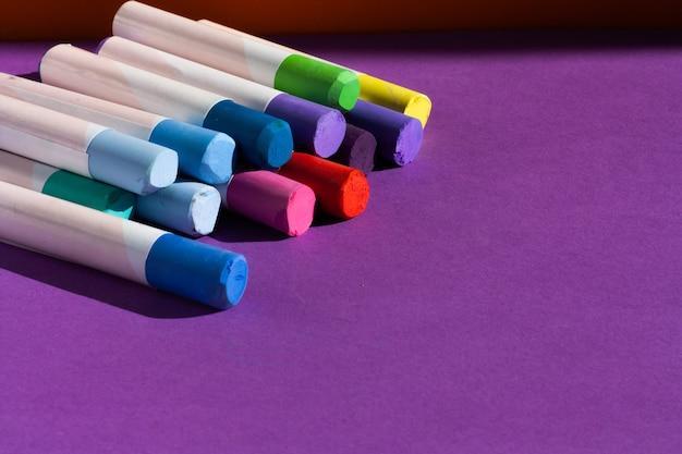 Künstlerkreide auf lila hintergrund. werkzeuge für kreative freizeit und malerei hobby. speicherplatz kopieren.