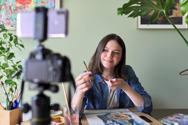 Künstlermädchen malt mit aquarellen und macht videos für ihren kanalblog. mädchen, das zeigt, was ihre anhänger, kinder und jugendliche, anzieht und lehrt. ausbildung, bildung, art direction