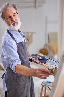 Künstlermalermann, der bild auf leinwand malt. happy retirement lifestyle-konzept