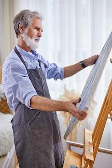 Künstlermann, der leinwand sein meisterwerk betrachtet, stehend denkt, in kontemplation, genießt zeichnen, malen