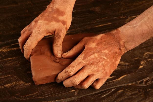 Künstlermannhände, die roten lehm für handcraft bearbeiten