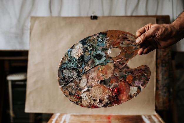 Künstlerpalette mit verschiedenen farben vor einem leeren papier. malerpalette als kunstwerk.