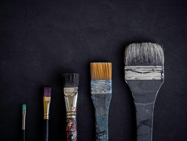 Künstlerpinsel viele größen, die als stufen- oder wachstumsgeschäftsgraph auf dunkler oberfläche angeordnet sind