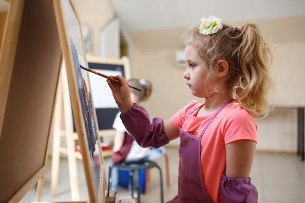 Künstlerschulmädchen, das aquarellpinsel in der werkstatt malt