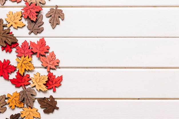 Künstliche ahornblätter auf weißem hölzernem hintergrund