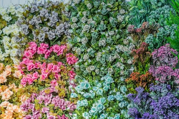 Künstliche blühende rosen des orange, blauen und rosa farbhintergrundes