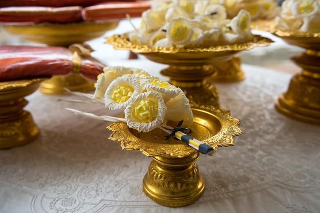 Künstliche blumen des sandelholzes und gelbe mönchrobe auf goldenem behälter für verbrennung