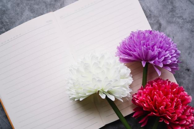 Künstliche chrysantheme blüht auf einem offenen notizbuch mit einer zeile