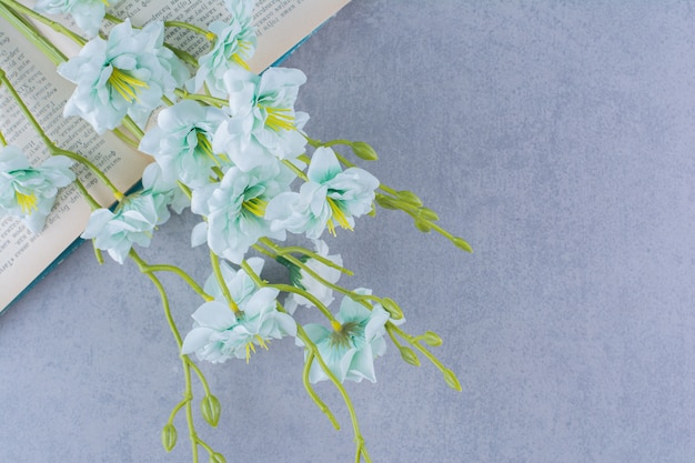 Künstliche madonna-lilienblume auf offenem buch platziert.