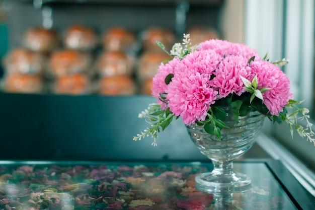Künstliche rosa blume auf glastisch mit kopienraum für liebeshintergrund