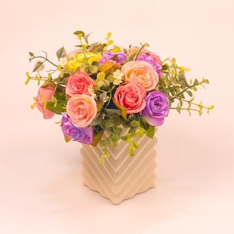 Künstliche rosafarbene blume der weinlese im vase auf weißem hintergrund