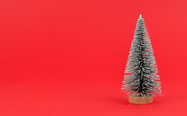 Künstlicher mini-weihnachtsbaum auf rotem hintergrund