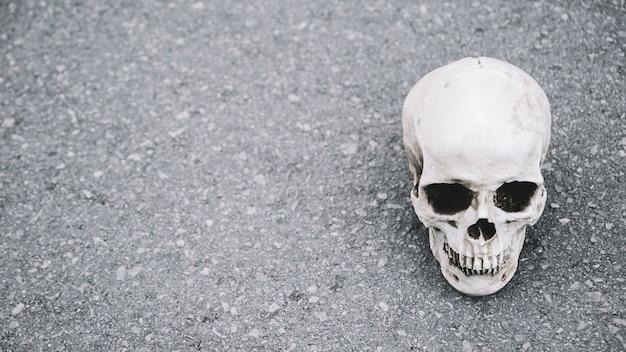 Künstlicher schädel des mannes liegend auf asphalt auf seite