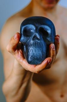 Künstlicher schädel in der hand eines starken mannes
