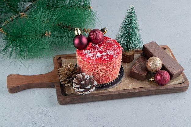 Künstlicher tannenzweig neben einem tablett mit verschiedenen desserts auf marmorhintergrund.