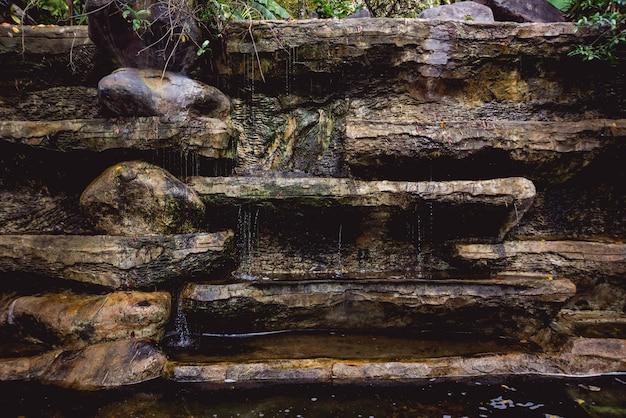 Künstlicher wasserfall im botanischen garten. steine und wasser