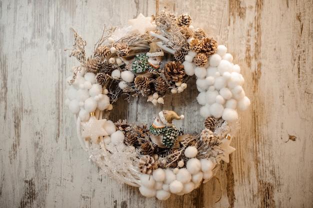 Künstlicher weihnachtskranz mit kleinen weißen wattebällchen, zapfen und spielzeugvögeln