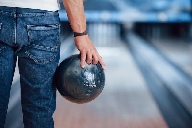 Künstliches licht. hintere partikelansicht des mannes in der freizeitkleidung, die bowling im club spielt