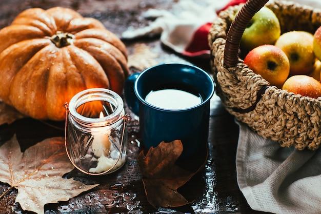 Kürbis, äpfel und tee auf holztisch