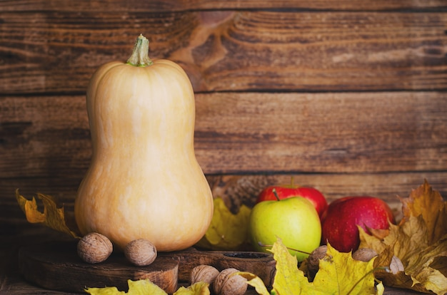 Kürbis, äpfel und walnüsse auf rustikalem hölzernem hintergrund