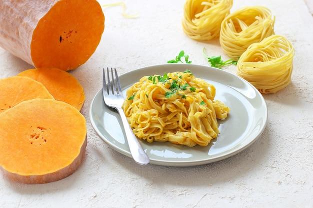 Kürbis alfredo fettucine pasta in einer keramikplatte mit frischen rohen butternut-kürbis-scheiben. herbstessen zum mittagessen. butternut-kürbis-rezept.
