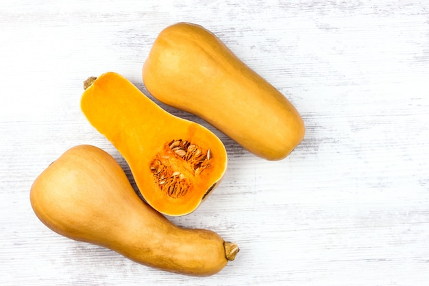 Kürbis auf einer weißen tabelle. süßer birnenförmiger kürbis mit drei orangen