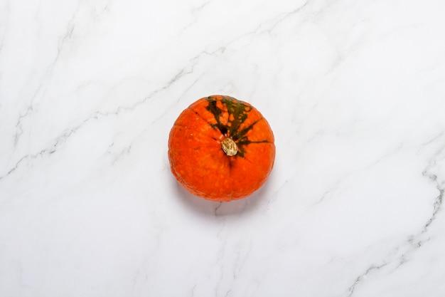 Kürbis auf marmoroberfläche. konzept halloween, herbst, ernte. flachgelegt, draufsicht