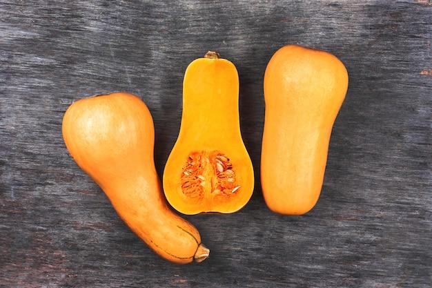 Kürbis auf schwarzem holztisch. süßer birnenförmiger kürbis mit drei orangen. halber kürbis in der mitte geschnitten