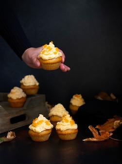 Kürbis-cupcakes auf einem dunklen hintergrund. weibliche hand, die cupcake hält. herbsthintergrundkürbisse und -blätter. kürbisbonbons. halloween und thanksgiving süßigkeiten. selektiver fokus. copyspace. vertikale