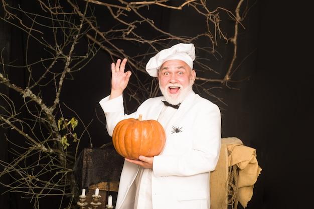 Kürbis für halloween bärtiger koch in kochmütze mit kürbis kochmann in weißer schürze mit kürbis für