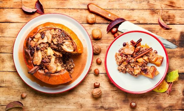 Kürbis gefüllt mit müsli und trockenfrüchten auf altem holztisch