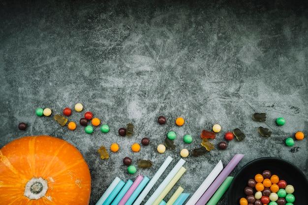 Kürbis in der nähe von strohhalmen und süßigkeiten